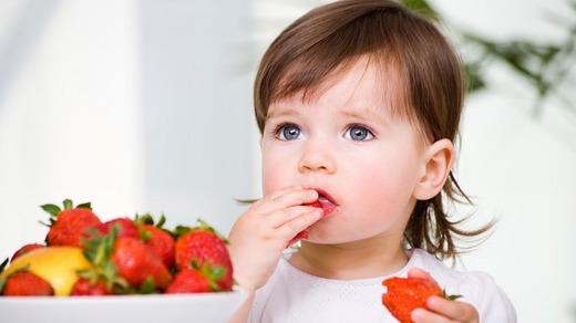 Девочка ест клубнику