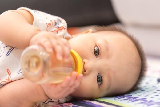 Малыш пьет чай из бутылочки