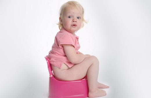 Девочка одетая в розовое сидит на горшке