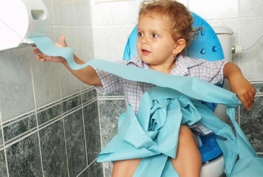 Девочка на унитазе берет туалетную бумагу