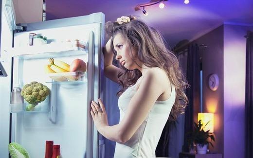 Девушка думает возле холодильника