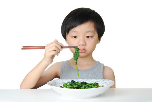 Мальчик питается зеленым салатом