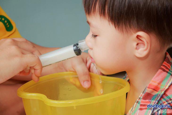 Промывание носа ребенку с помощью шприца