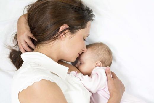 Женщина кормит грудью своего ребенка
